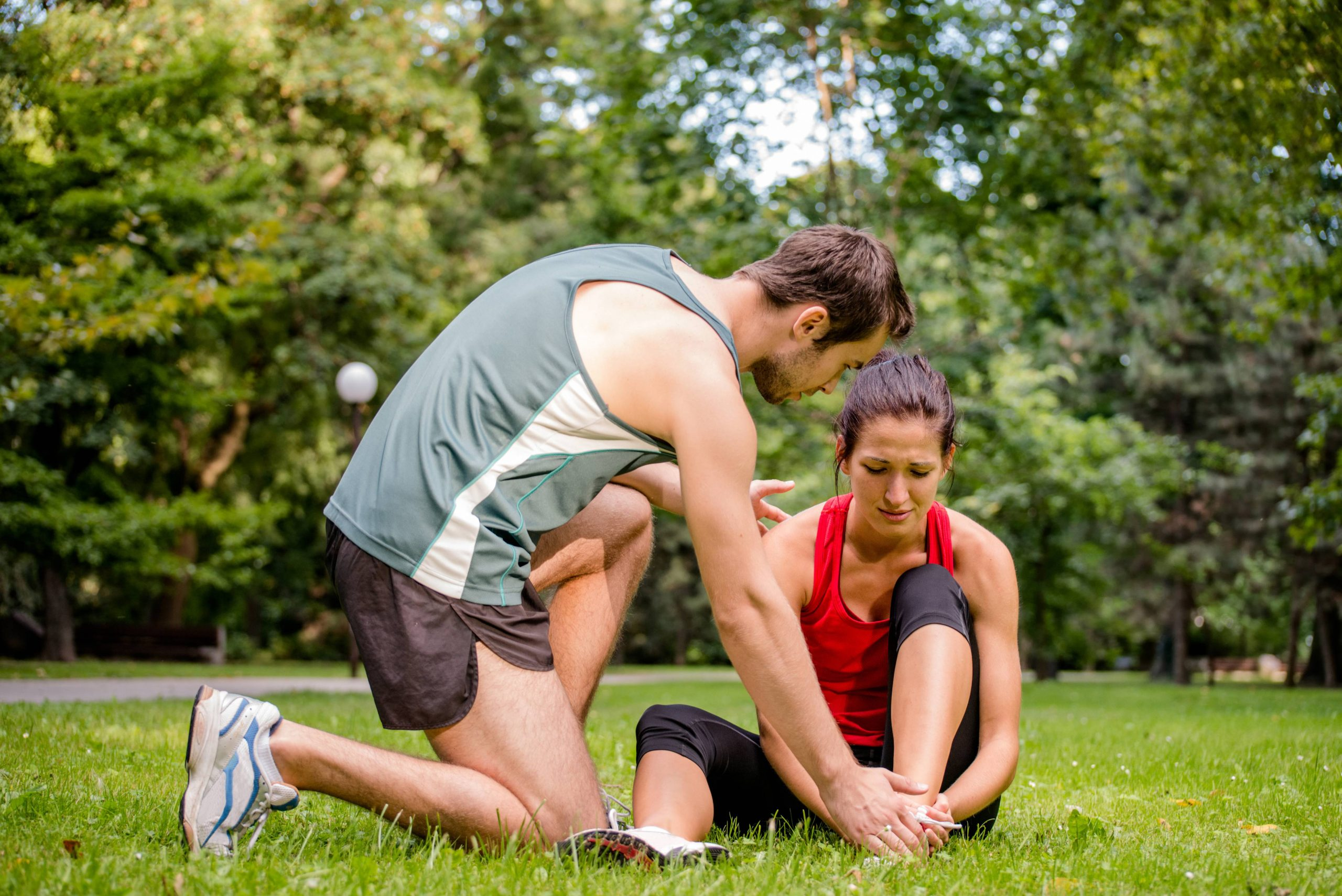 A wan helping a lady stting on the ground in the park who got injujred her ankle while exercising