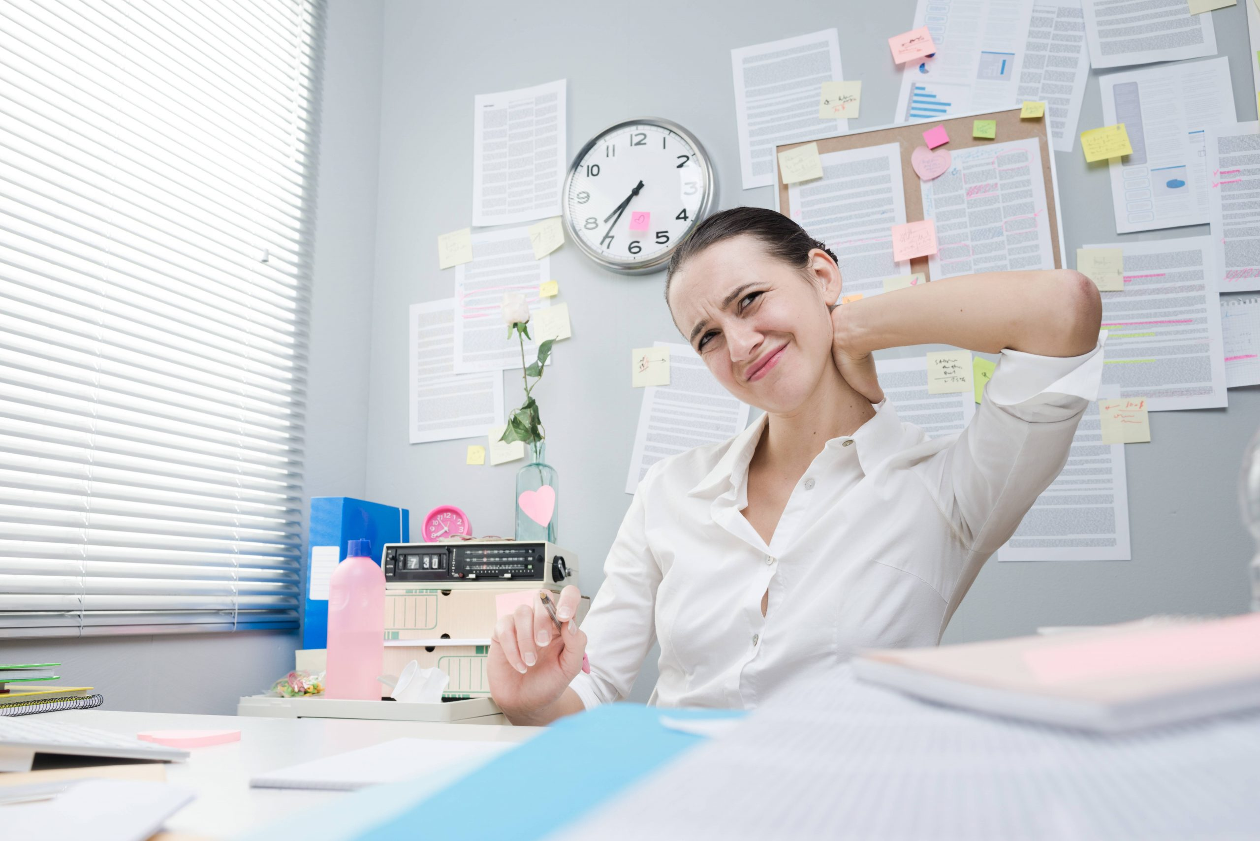 A woman holding her neck feeling neck pain while working in her office